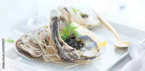 Fresh oysters with black caviar. Opened oysters with black sturgeon caviar. Gourmet food. Delicatessen