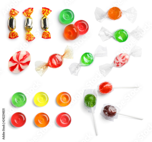 Set with different candies on white background, top view