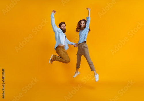 Obraz na plátně couple of emotional people man and woman jumping on yellow background