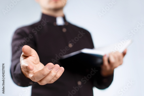 Obraz na płótnie Young priest reading the Holy Bible and stretching his hand on neutral backgroun