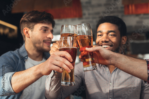 Fotografía Male friends drinking beer and clinking glasses at bar
