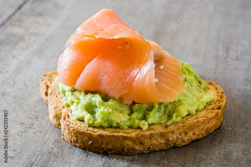 Close up avocado toast with fresh salmon on wooden table