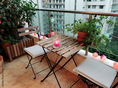 Photo Lovely decoration for terrace with plants, table, chairs and candle
