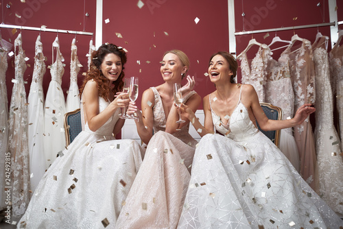 Stampa su Tela Full length of happy brides with champagne glasses