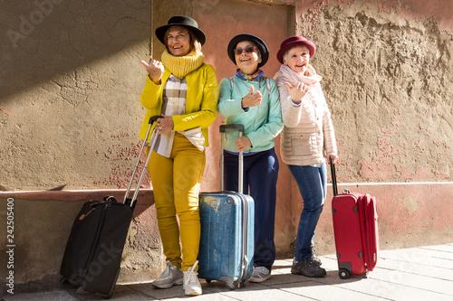 Tre simpatiche amiche di età matura in viaggio con il cappellino e il trolley fanno l'autostop sorridendo