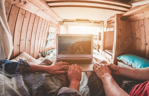 Fototapeta Digital nomad couple working inside minivan with wood interiors