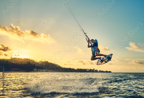 Young man kite boarder jumps over the sea at sunset