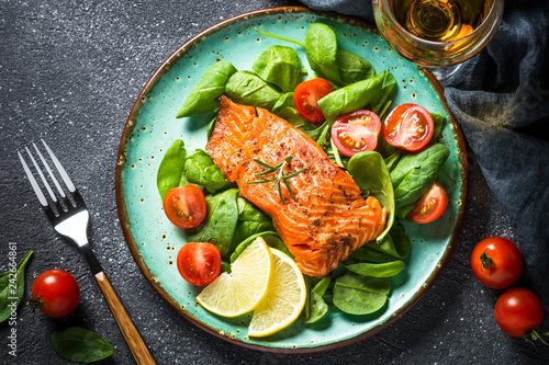 Canvas Print Baked salmon fish fillet with fresh salad top view.