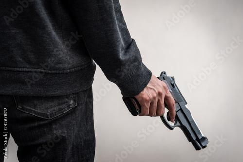 Obraz na płótnie A man holding a gun in hand, the ship ready to shoot the man pointed a gun at us