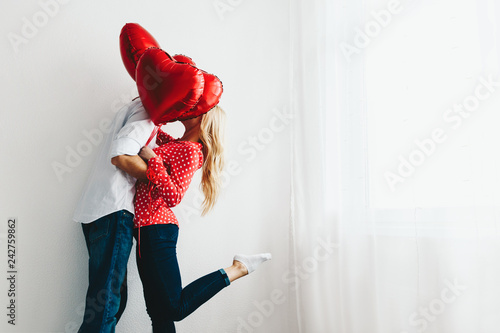 Couple. Love. Valentine's day. Emotions. Man and woman are kissing behind the red heart-shaped balloons