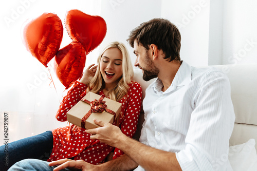 Couple. Love. Valentine's day. Emotions. Man is giving a gift box to his woman, both smiling; at home
