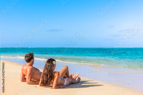 Couple on beach travel honeymoon vacation lying down sunbathing relaxing on luxury holiday in idyllic destination. Young tourists in love.