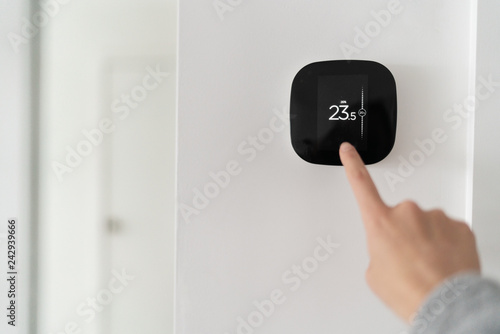 Smart home digital thermostat touch screen woman touching touchscreen to adjust temperature of heating in living room wall.