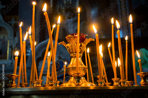 Fotografie, Obraz Many burning wax candles in the orthodox church or temple