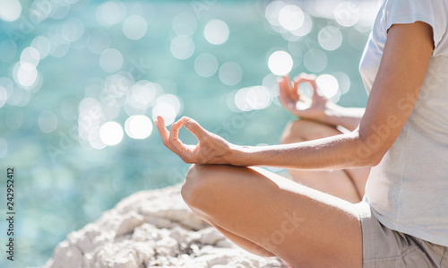Young woman practicing yoga near the sea in summer. Harmony and meditation concept. Healthy lifestyle. Enjoying life, summer fun, self care, mindfulness concept