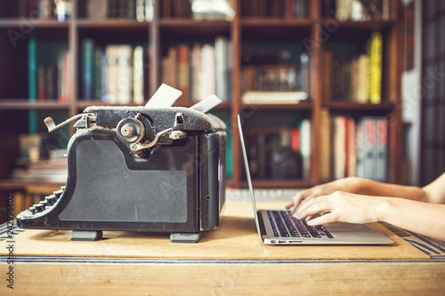 woman hands type on modern notebook. old vintage dust-covered typewriter with sheet of white paper near modern notebook on bookcase background. modern technology and vintage appliances