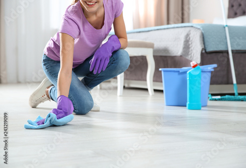 Young woman washing floor with rag and detergent in bedroom, closeup. Cleaning service