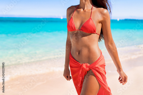 Red coral bikini body sexy swimsuit model woman showing off toned stomach abs and slim waist wearing sarong pareo fashion clothes on beach. Lower body crop of torso and hips.