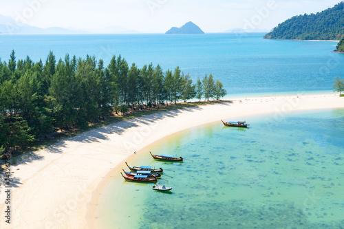 Fototapeta premium piękna sceneria z drewnianą łodzią na plaży biały piasek w błękitne morze i błękitne niebo na tropikalnej plaży.