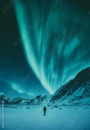 Canvas Print Young man watching Aurora Borealis in winter, Lofoten, Norway