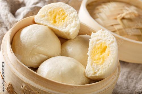 Chinese custard buns closeup in bamboo steamer. horizontal