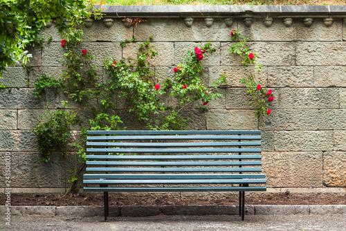 Empty blue wooden bench stands near stone wall Fototapeta