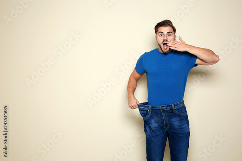 Fit man in oversized jeans on color background, space for text. Weight loss