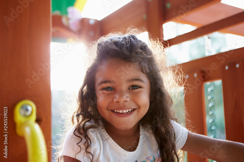 Fototapeta Young Hispanic girl playing on a climbing frame in a playground smiling to camer