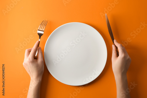 Fototapeta Female hands with cutlery and empty plate on color background