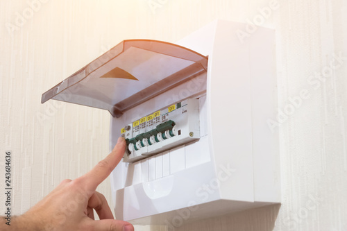 Circuit breaker board displays many switches. A finger is about to turn it back on