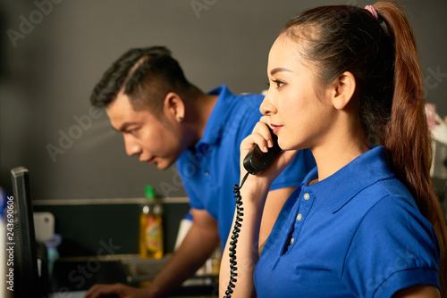Young Asian sales manager talking on phone with customer