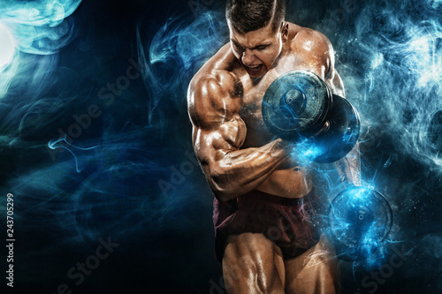 Canvas Print Brutal strong muscular bodybuilder athletic man pumping up muscles with dumbbell on black background