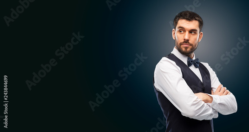 Photo people concept - serious man in white shirt, waistcoat and bowtie over black bac