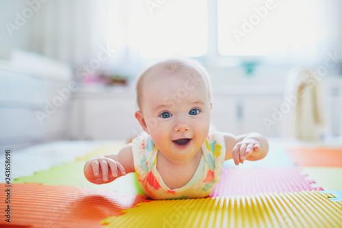 baby girl lying on colorful play mat on the floor Fototapeta