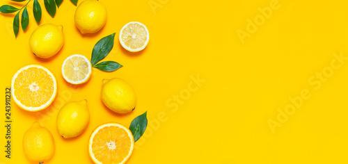 Fotografie, Obraz Ripe juicy lemons, orange and green leaves on bright yellow background