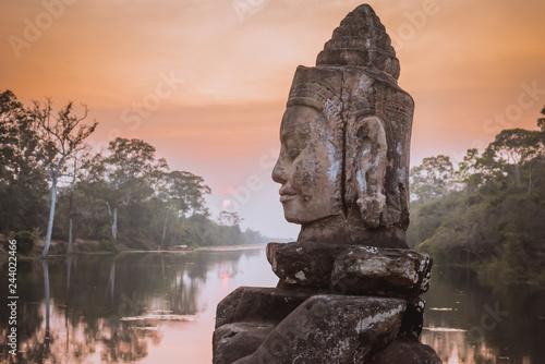 Fototapeta premium Kamienny Asura na grobli blisko Południowej bramy Angkor Thom w Siem Przeprowadza żniwa, Kambodża. Piękny zmierzch nad antyczną fosą w tle. Angkor Thom jest popularną atrakcją turystyczną.