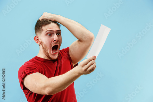 Foto Young boy with a surprised happy expression bet slip on blue studio background