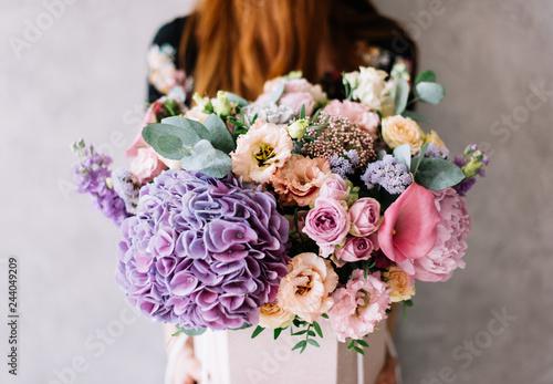 Very nice young woman holding beautiful blossoming bouquet of fresh hydrangea, c Fototapeta