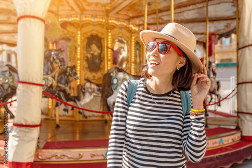 Carta da parati Happy asian woman traveler at the fairy carousel horses in amusement park