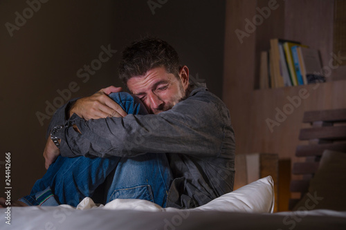 Fotografie, Obraz young crazy desperate and depressed man crying on bed suffering anxiety crisis a