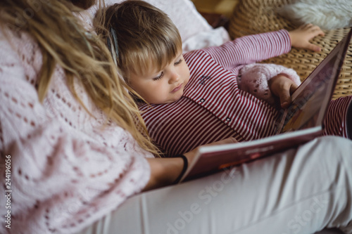 A young mother and son are reading a fairy tale book near the fireplace.