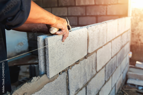 Tableau sur Toile Worker building wall bricks with cement