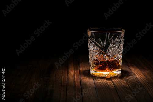 Fotografija Crystal glass of whiskey on a wooden table on a black background
