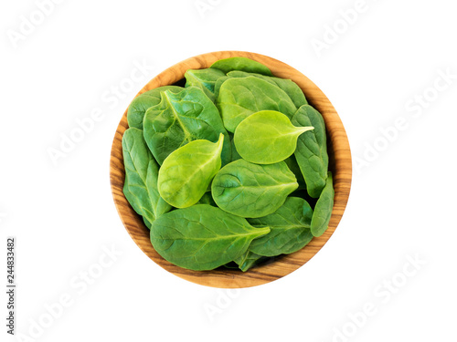 Spinach leaves in the olive wood bowl top view