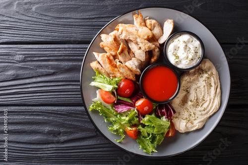 Mediterranean Chicken Shawarma Bowl with hummus, vegetables salad and sauce close-up. Horizontal top view