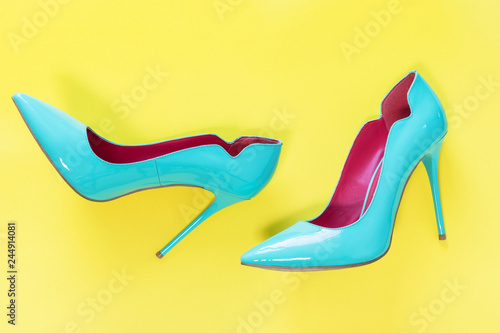 Fotografie, Tablou Pair of Blue high heels glassy shoes on yellow background, top view