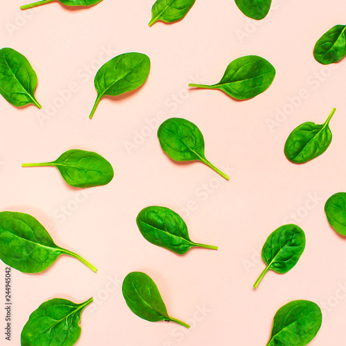Fresh green spinach leaves pattern on pink background Flat lay top view. Creative food concept. Ingredient for salad. Vegetable pattern design. Healthy lifestyle.