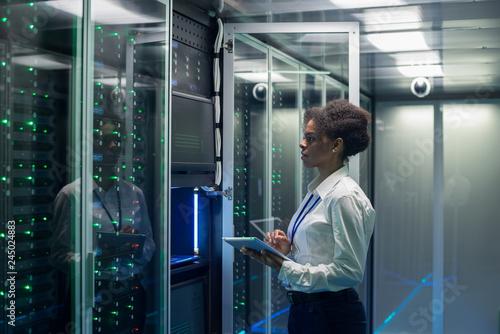 Carta da parati Medium shot of female technician working on a tablet in a data center full of ra