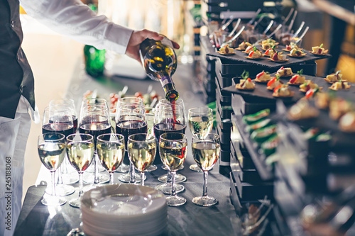 The waiter pours wine into glasses. Event catering concept. Poster Mural XXL
