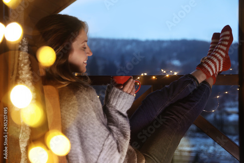 Fotografia Woman with cup of hot beverage and Christmas lights resting on balcony